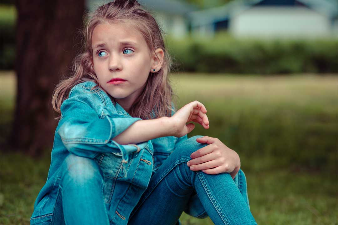 girl in park with worried look on her face